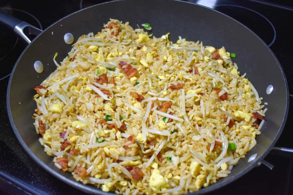The completed bacon fried rice in a large, black skillet.