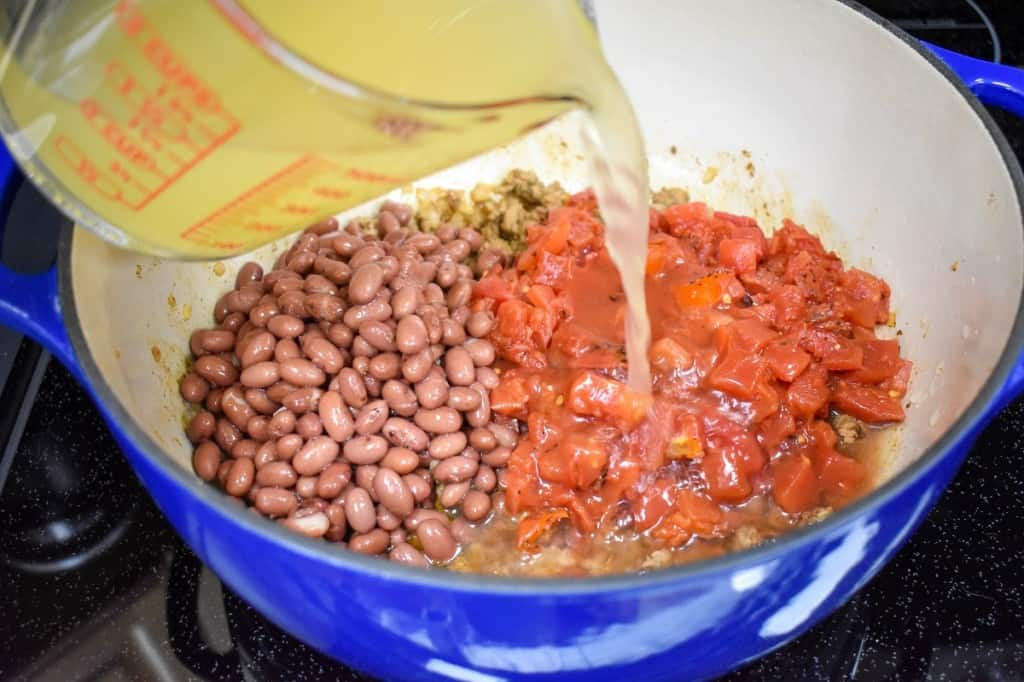Chicken broth being added to diced tomatoes and red beans in a large blue pot with an off-white interior.
