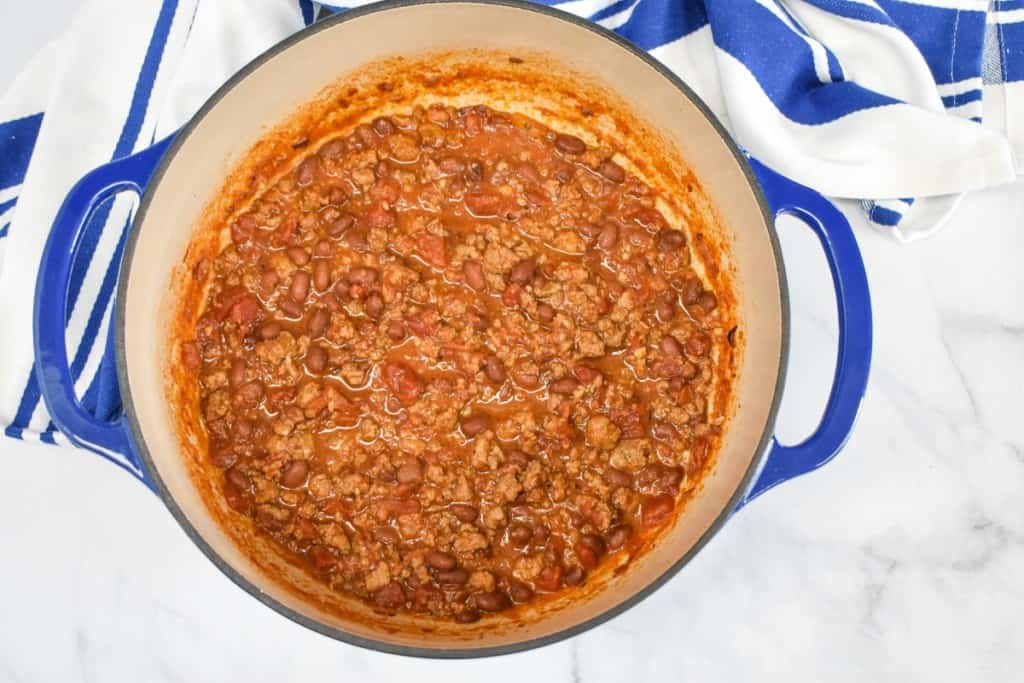 An image of the cooked chili, still in the blue pot with a blue and white linen on a white table.