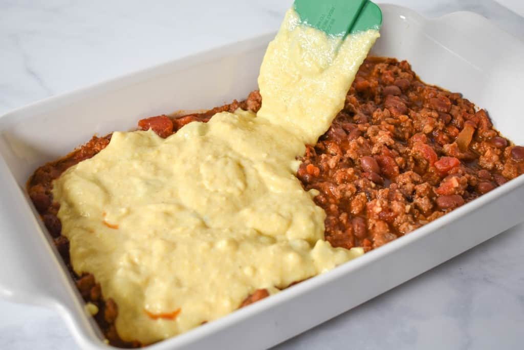 The chili in a white casserole dish with cornbread mix being added to the top.