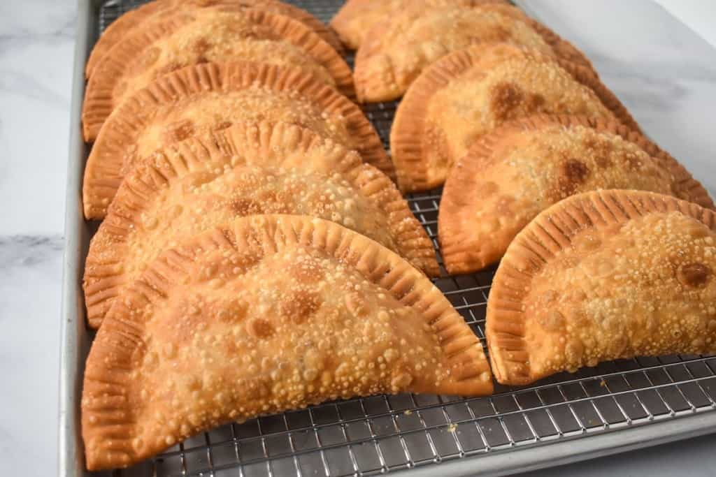 An image of ten fried empanadas arranged on a baking sheet lined with a cooling rack.