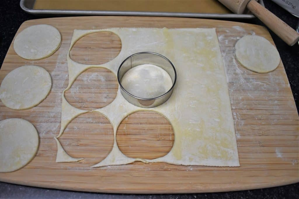 Puff pastry cut into rounds on a lightly floured cutting board