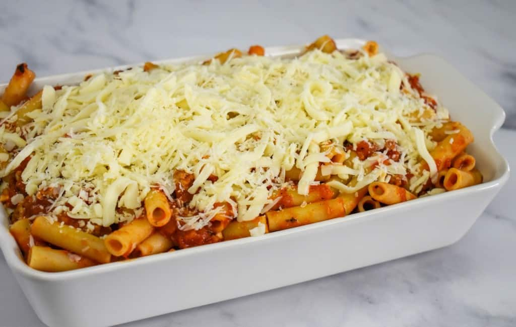 The prepared ziti, sauce and cheese in a white casserole dish, before baking.