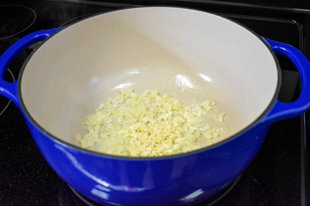 Diced onions and garlic cooking in a large blue pot.