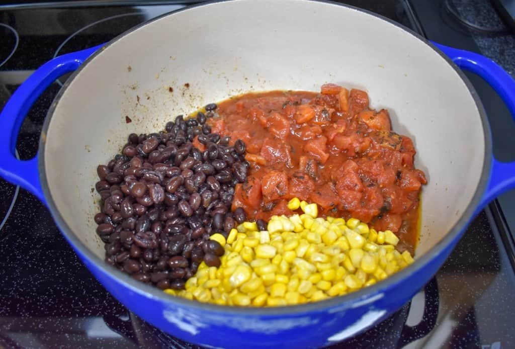 Black beans, diced tomatoes and corn in a large blue pot with a white inside.
