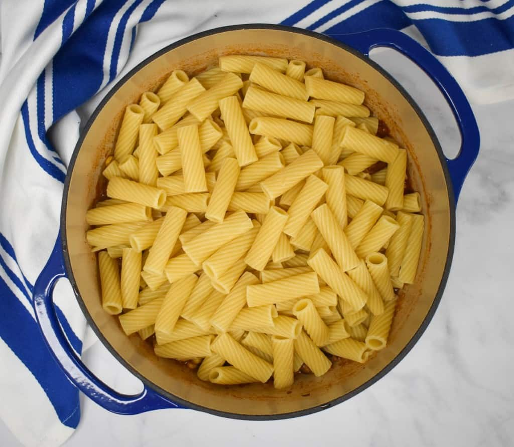An overhead image of the pasta set on top of the sauce, it's still in the blue pot with a blue and white striped kitchen towel on a white table.