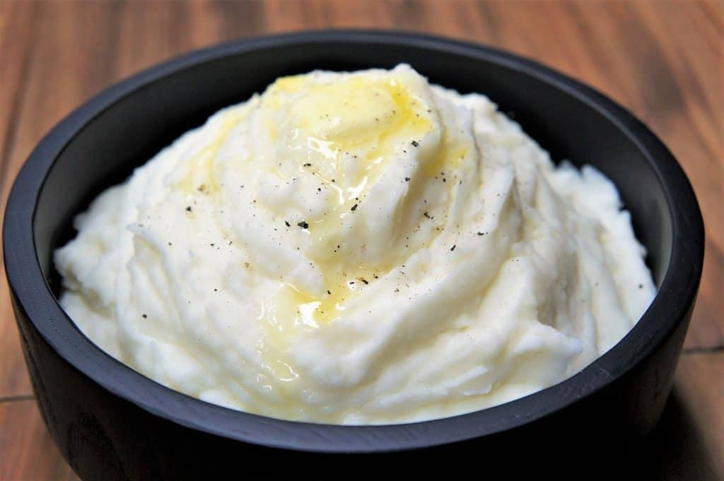Mashed Potatoes with melted butter on top served in a black serving bowl
