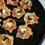 A top picture of mini taco bites arranged on a round, black serving tray.