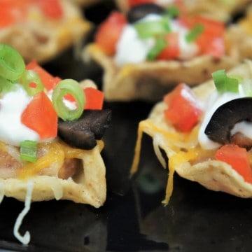 Mini taco bites arranged on a black serving tray.