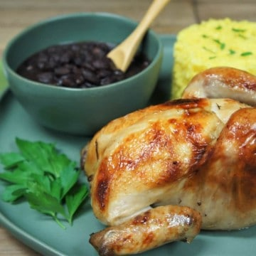 A whole Cornish hen served on a large green plate with yellow rice and a bowl of black beans in the background.