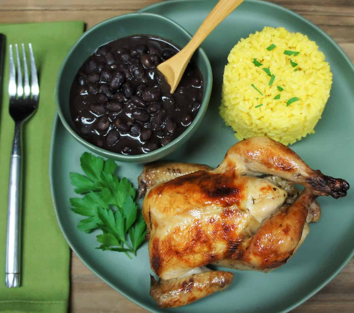 A whole Cornish hen served on a green plate with yellow rice and black beans.
