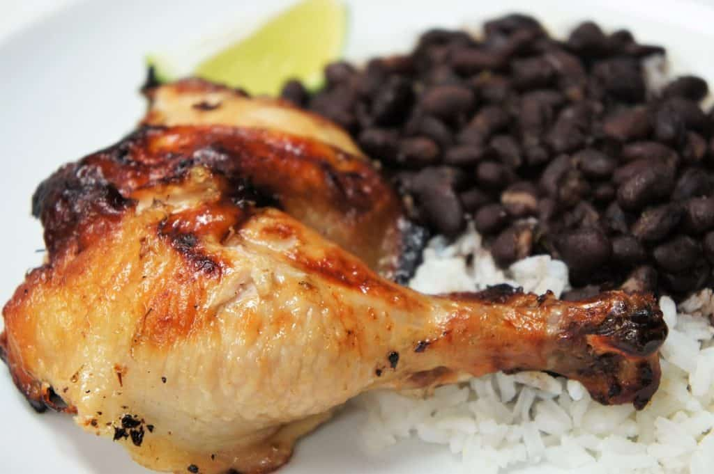 Mojo Marinated Grilled Chicken leg and thigh served with rice and black beans