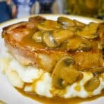 A thick pork chop covered with mushroom gravy on a bed of mashed potatoes, served on a white plate.