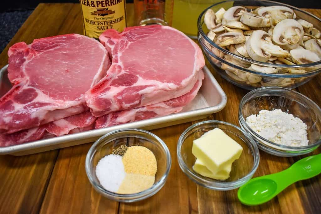 The ingredients for the mushroom pork chops recipe, prior to cooking, displayed on a wood cutting board.