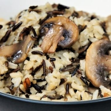 Mushroom Rice Pilaf, white and wild rice topped with golden mushrooms served in a shallow bowl
