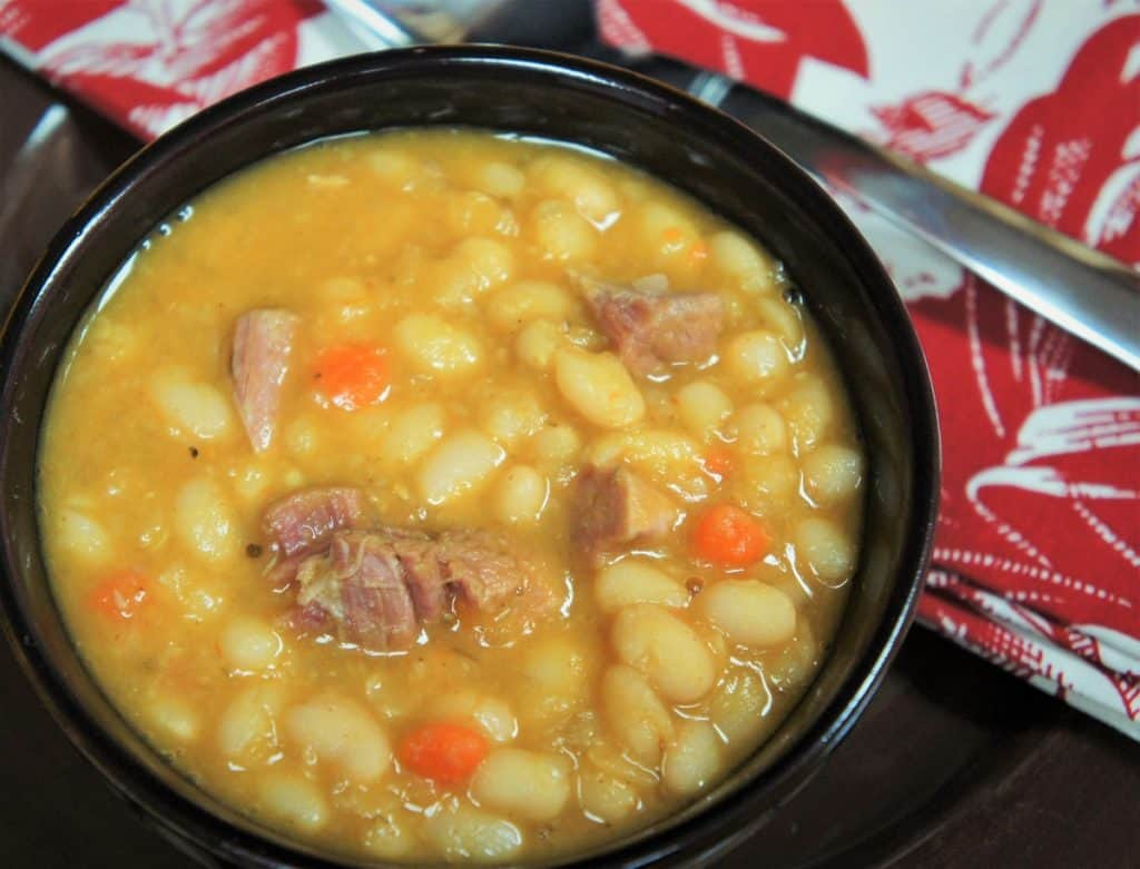 Navy Bean Soup with pieces of smoked ham served in a black bowl