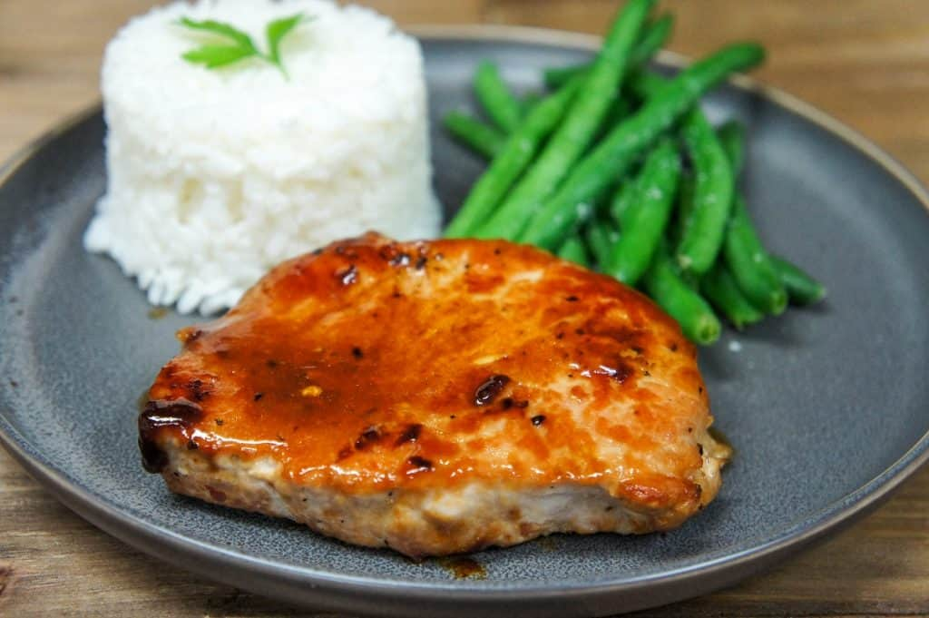 The orange glazed pork chop served on a gray plate with white rice and green beans.
