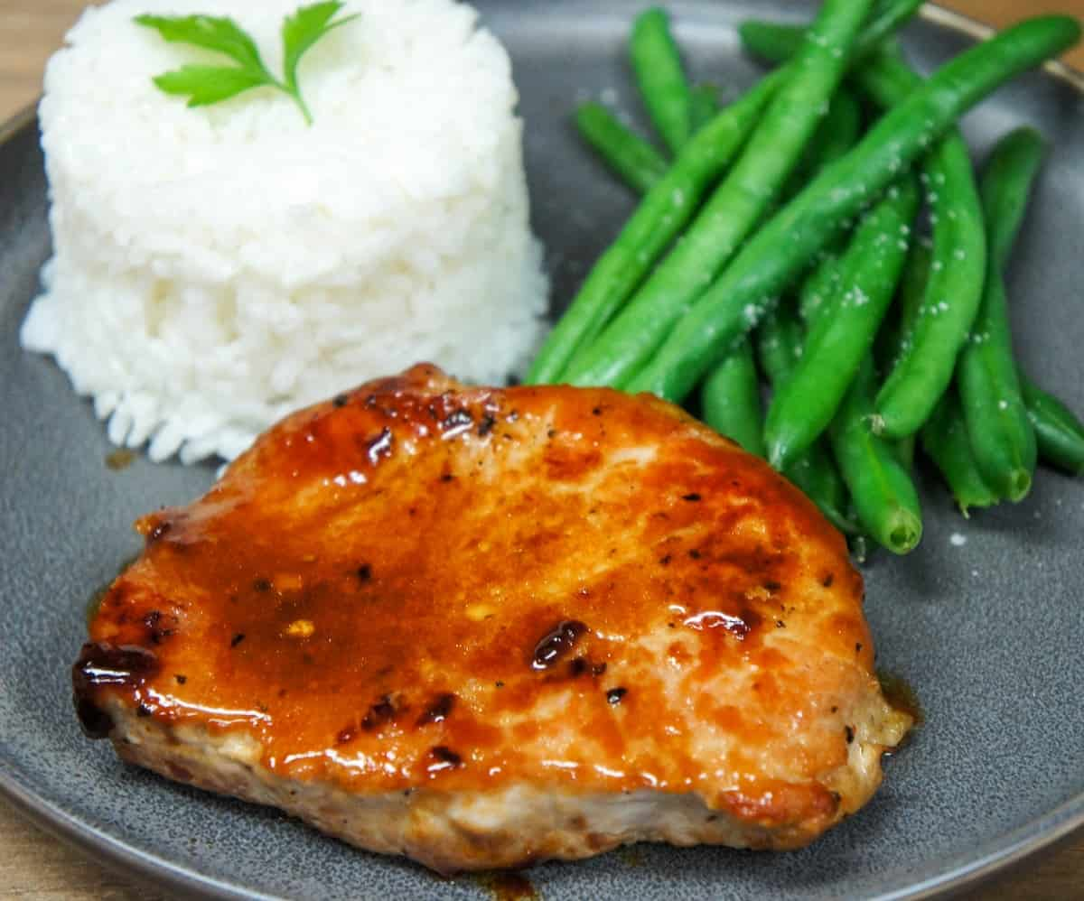 The pork chop served with white rice and green beans on a gray plate.