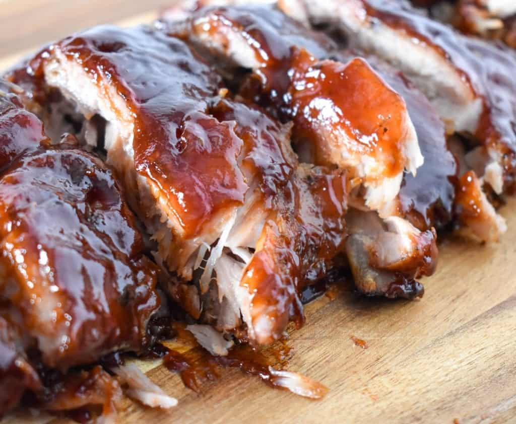 A close up of the sliced ribs on a wood cutting board.