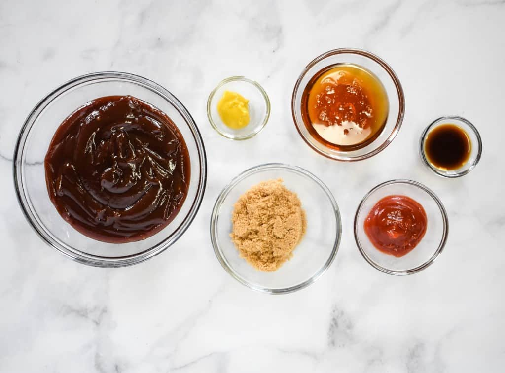 The ingredients for the rub and the sauce separated in clear bowls and arranged on a white table.