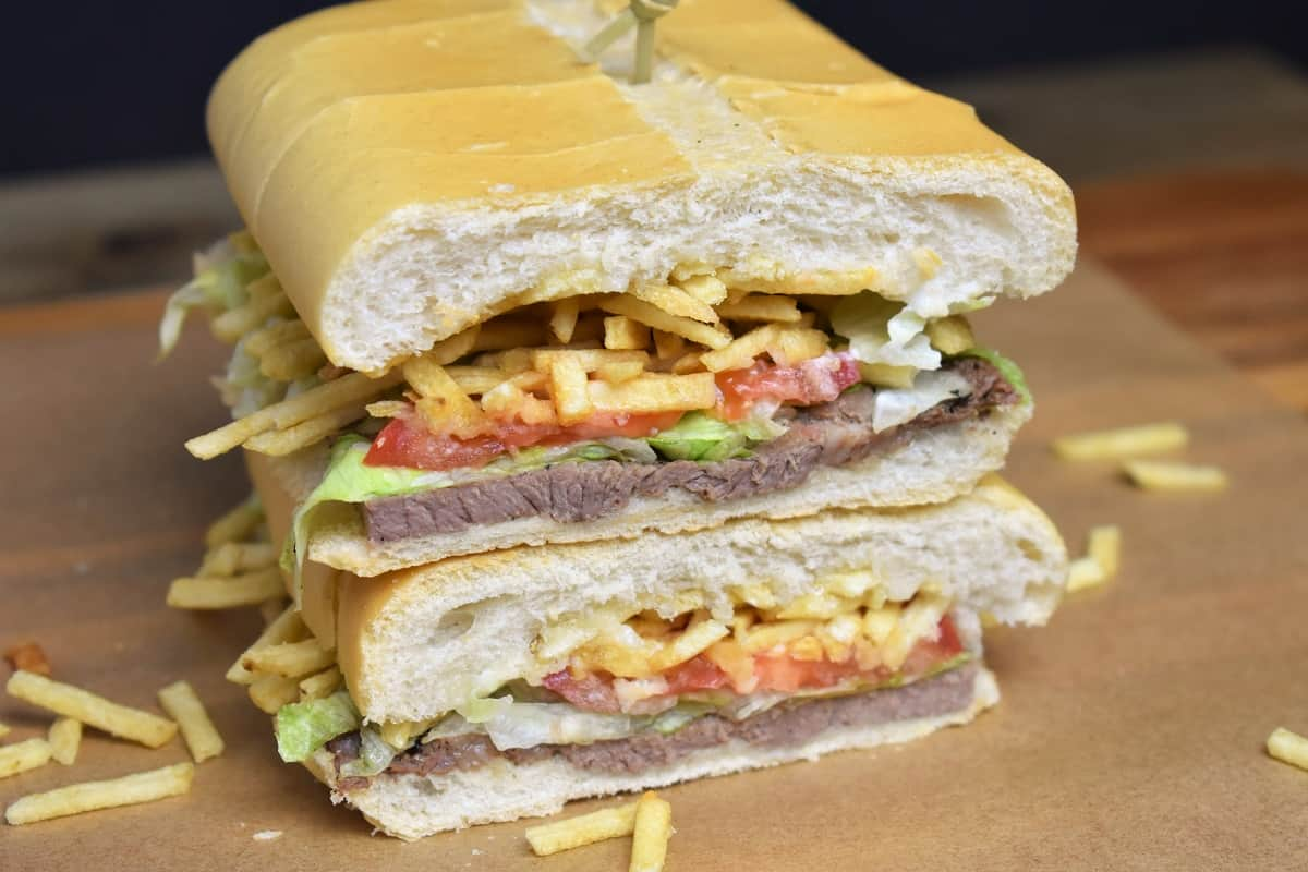 Pan Con Bistec, a thin cut steak served on Cuban bread with lettuce tomatoes and potato sticks