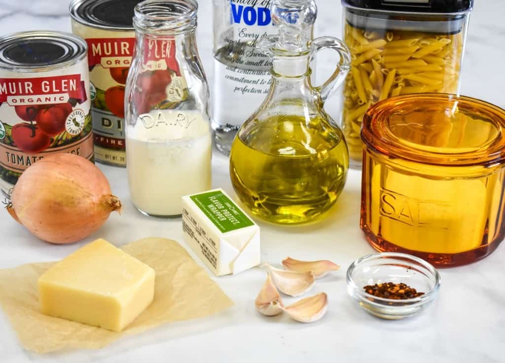 The ingredients for the pasta with vodka sauce, before prepping, arranged on a white table.