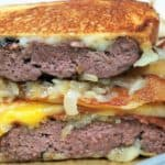 Patty Melts cut in half, stacked with grilled onions and melted cheese