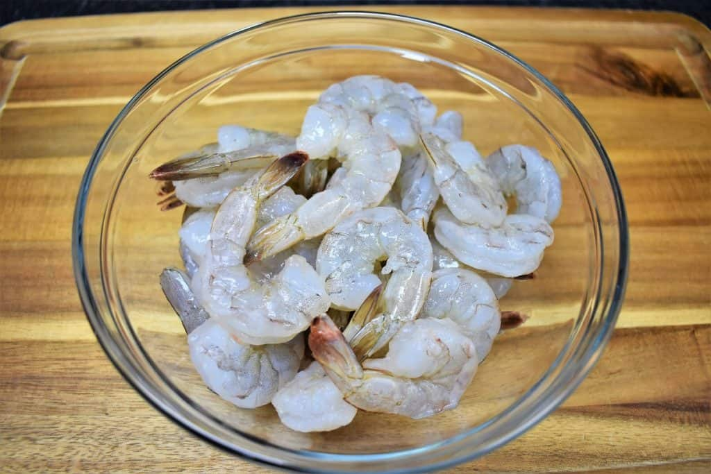 Peeled large shrimp in a clear bowl displayed on a wood cutting board.