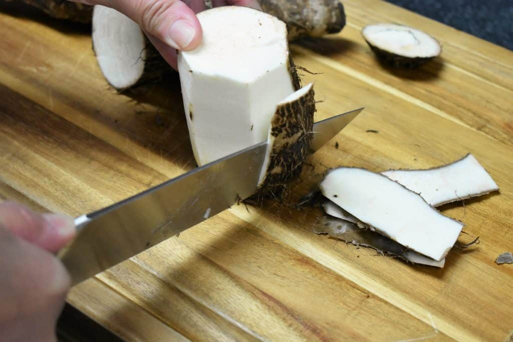 Peeling a Malanga on a wood cutting board