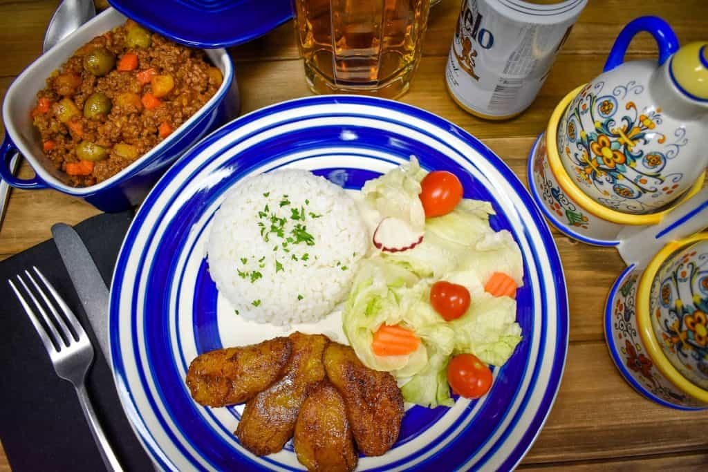 Picadillo served in a blue crock with a blue and white plate with white rice, fried sweet plantains and a salad on the side.