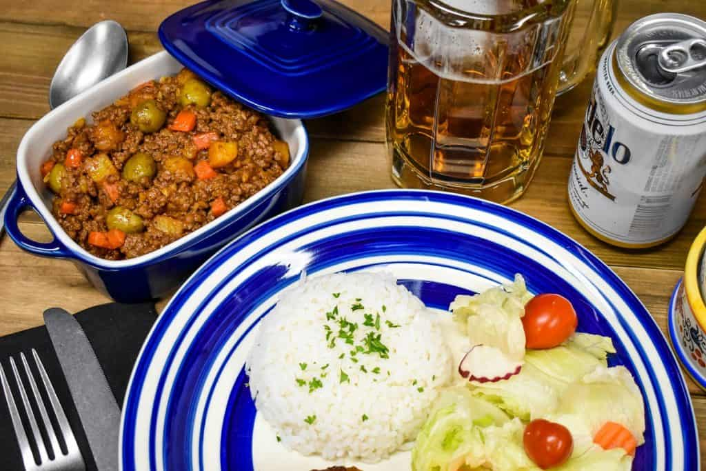 Picadillo served in a blue crock with a plate of white rice and salad on the side.
