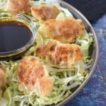 Pork potstickers arranged on a bed of shredded lettuce on a gray plate with a small bowl of soy sauce in the middle.