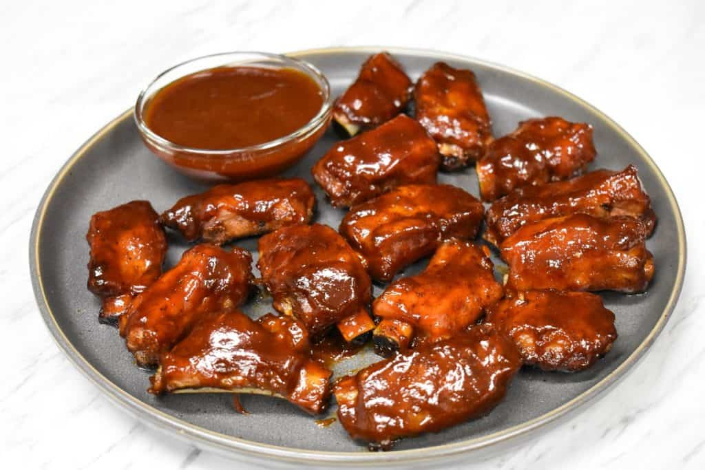 Pork riblets arranged on a large gray plate with a small bowl of barbecue sauce.