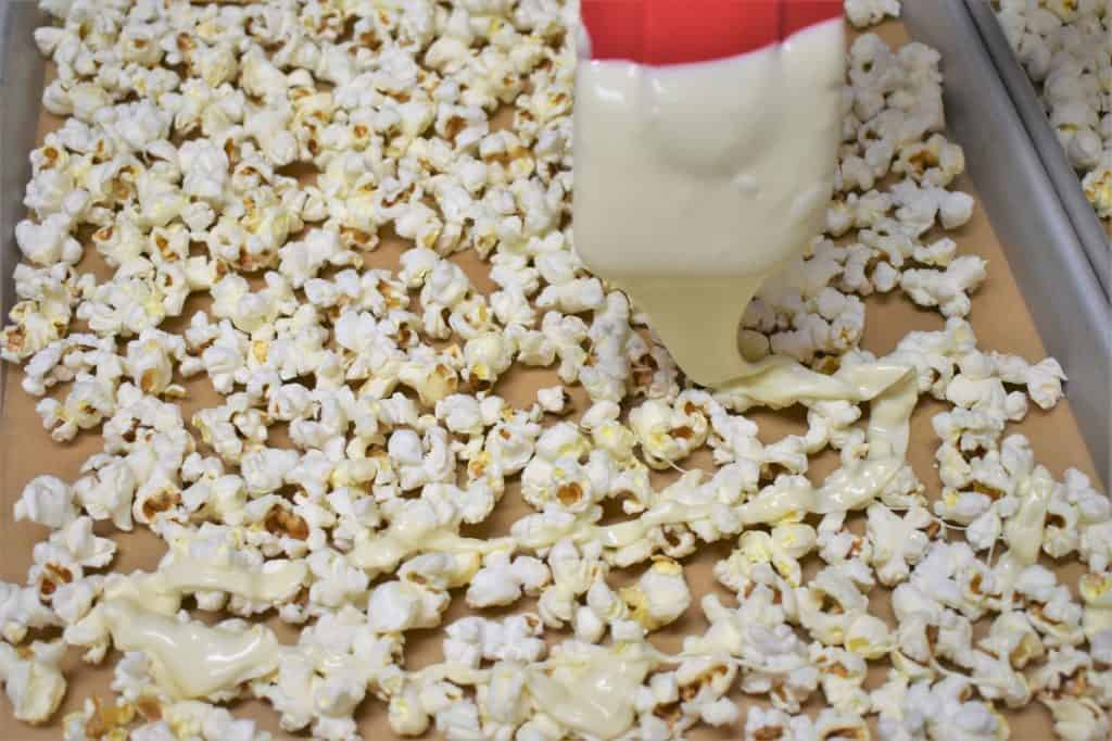 Drizzling White Chocolate on Popcorn using a red spatula
