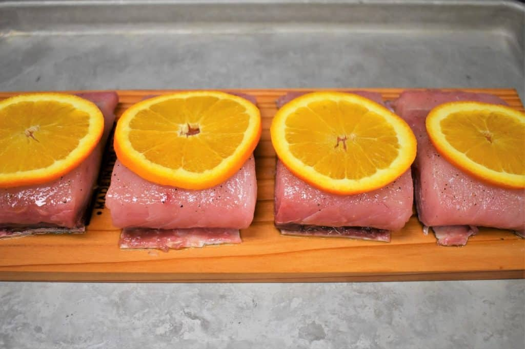 Four mahi mahi fillets arranged on a cedar plank and topped with an orange slice.