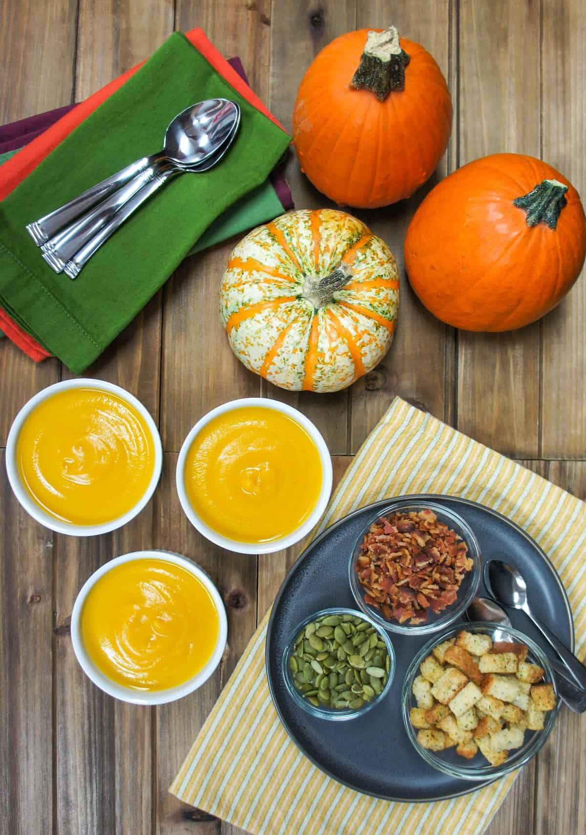 Three small bowls of soup set on a wood table with the garnishes in small bowls to the right, decorative pumpkins, linens and spoons to the left.