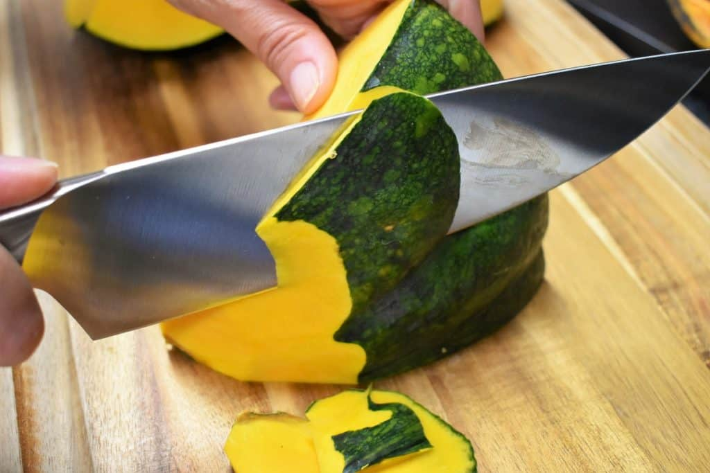 A pumpkin being peeled on a wood cutting board