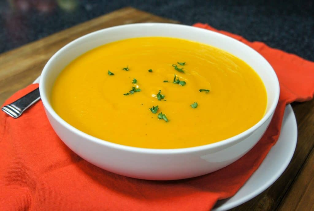 The creamy pumpkin soup served in a large white bowl set on an orange linen on a large white plate.