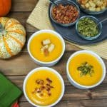 Three small bowls of the soup set on a wood table with the garnishes in the background, decorative pumpkins to the left with spoons and linens.