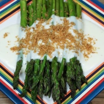 Roasted Asparagus, topped with mornay sauce and golden, breadcrumbs served on a multi-color plate