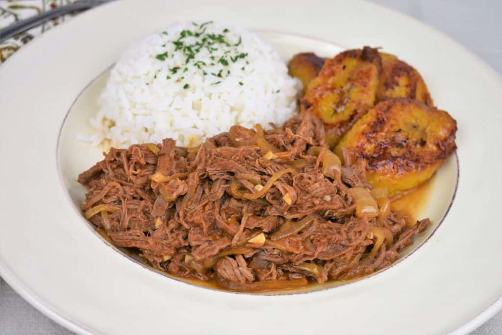 Ropa Vieja served with white rice and fried sweet plantains served on a white plate.