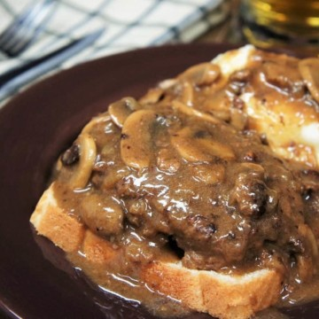 Salisbury Steak Open-Face Sandwich served with a side of mashed potatoes and covered with mushroom gravy on a brown plate