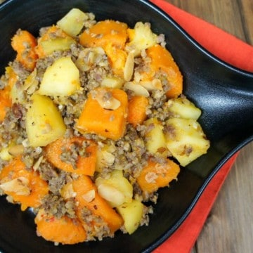 A close of the the sausage and butternut squash in a black serving skillet set on an orange linen on a wood table.