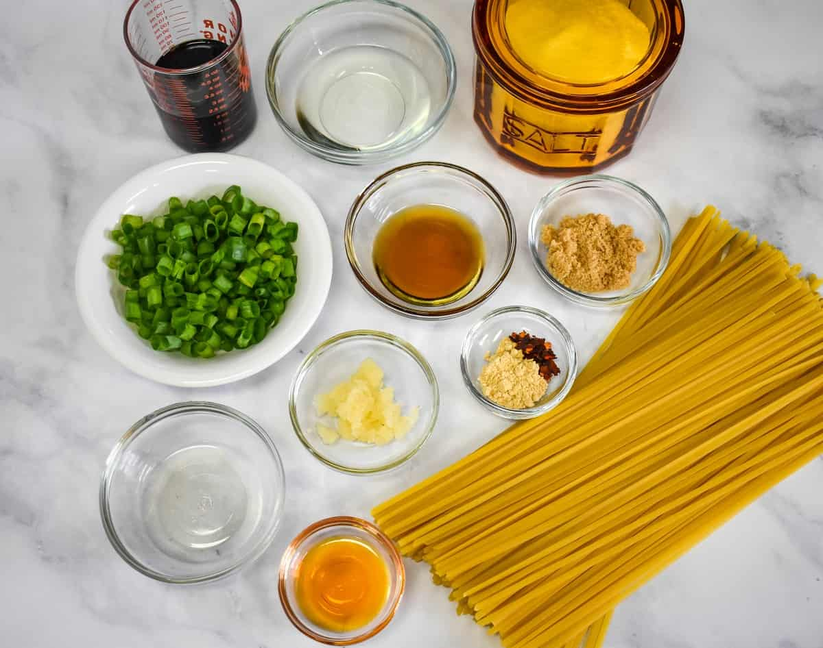 The prepped ingredients for the sesame noodles arranged on a white table.