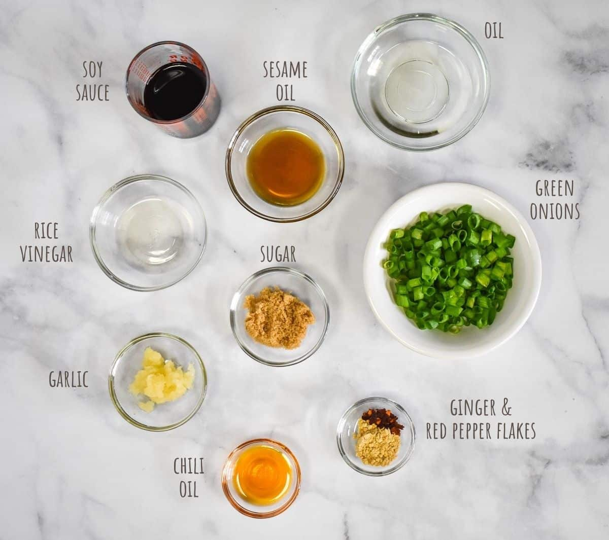 The ingredients for the sesame sauce arranged on a white tables in glass bowls. The image has the name of the ingredient in small letters next to each.