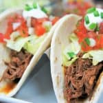 A close up of shredded beef in a soft tortilla shell topped with lettuce, diced tomatoes, sour cream and green onions.