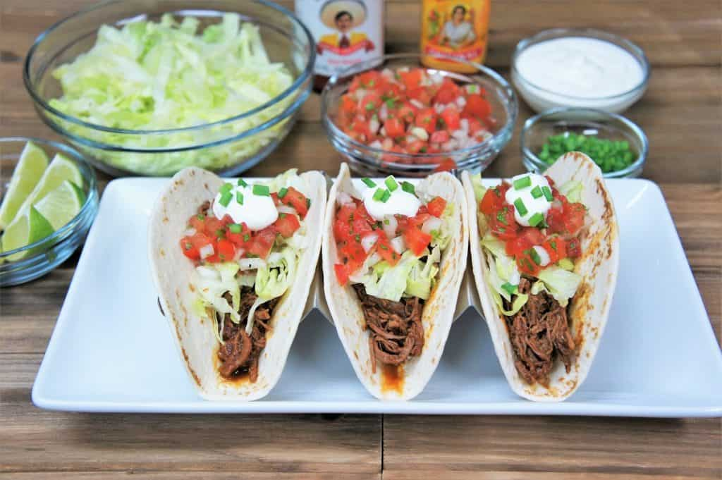 Three shredded beef tacos in a soft tortillas topped with lettuce, diced tomatoes, sour cream and green onions.