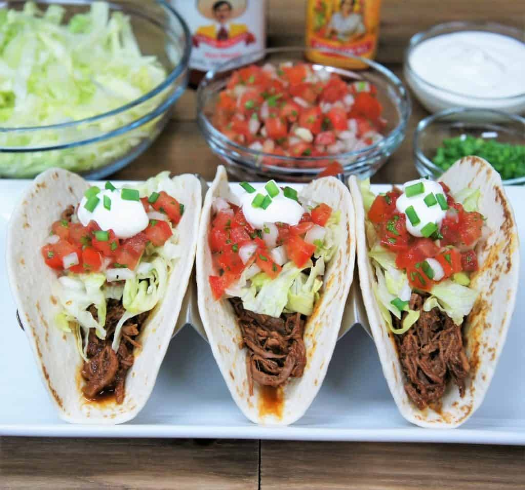 Three shredded beef tacos in soft tortillas topped with lettuce, diced tomatoes, sour cream and green onions.
