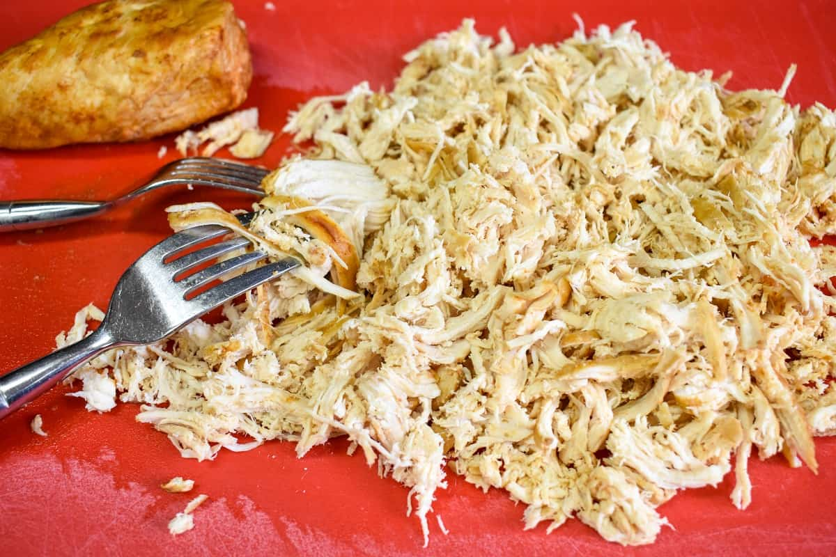 The cooked shredded chicken breast on a red cutting board with two forks.
