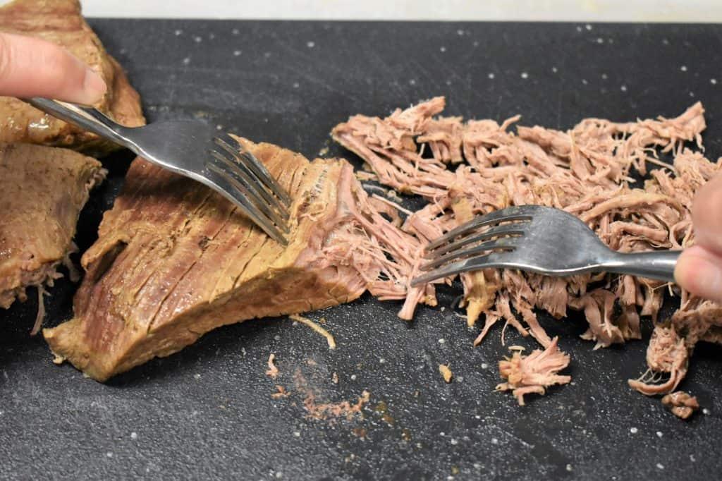 Flank steak being shredded on a black cutting board using two forks.
